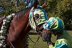 A woman jockey giving her winning horse a congratulatory kiss