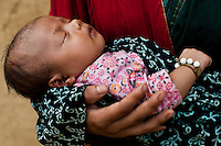 Nisha Darlami, 19, carries her 1 month old healthy baby girl, Bushpa, as she sits in her mother's house in Kalyan Village, Surkhet district, Western Nepal, on 30th June 2012. Nisha eloped with her step nephew when she was 13 but the couple used contraceptives for the next 6 years to delay pregnancy until she turned 18. In Surkhet, StC partners with Safer Society, a local NGO which advocates for child rights and against child marriage. Photo by Suzanne Lee for Save The Children UK