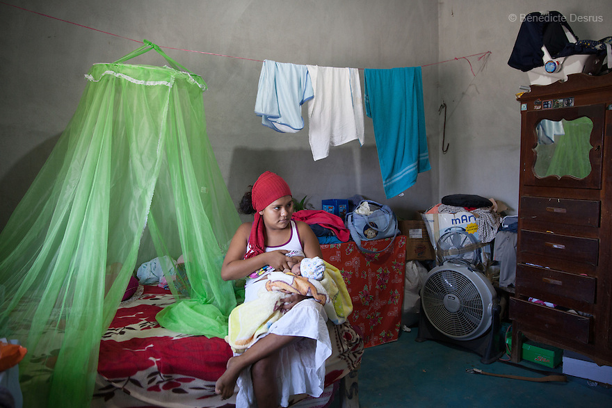 """Luz Betsaida Orozco Pineda and her new born baby at their home in Juchitán, Mexico on February 17, 2016. Now 14, Luz became pregnant when she was 13 after being """"stolen"""" according to the Zapotec Indigenous tradition. Considered a traditional kind of marriage – Luz is too young to wed legally – the custom dictates that the couple go to the young man's house and announce their plans to marry. While the family waits, the couple go to a room together; he emerges later with a blood-stained handkerchief to prove his bride's virginity. Luz, who started going out with the father of her baby when she was 10, lives with her in-laws in the 6 de noviembre neighbourhood on the outskirts of Juchitán in the southern Mexican state of Oaxaca. Her baby was born on January 13, 2016. Despite following tradition, she speaks little Zapotec – the language of her husband and his family – she follows tradition, wearing a headscarf to protect her health as she is still observing the 40-days quarantine period after giving birth, during which she stays in the house. While Mexico has outlawed marriage under the age of 18, many young girls become unofficial wives and mothers much earlier. In Juchitán, teenage pregnancy is expected, even prized. Mexico ranks first in teenage pregnancies among the member countries of the Organization for Economic Co-operation and Development(OECD). Photo by Bénédicte Desrus"""