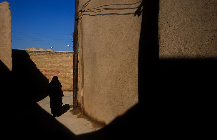 An Iranian woman passes through the narrow mud-brick lanes of Yazd, Iran, January 2006. A desert city considered to be among the world's oldest, Yazd'  ancient streets are a complex maze where motorbikes zoom around corners and on streets otherwise free of motorized traffic. Photo: Ed Giles.