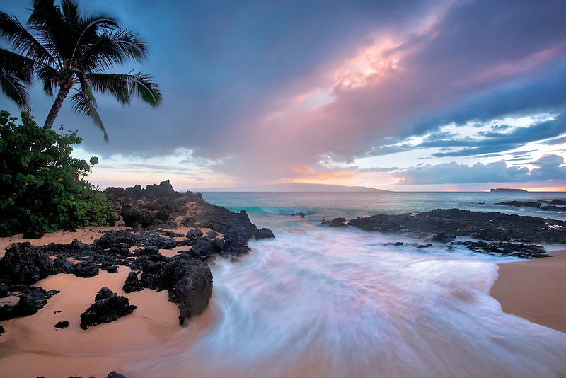 Sunset clouds and wave with palm trees. Maui, Hawaii.