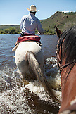 USA, Wyoming, Encampment, a wrangler leads riders across the North Platte River, Abara Ranch