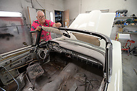 Robert Parker, a longtime classic car dealer, uses steel wool Friday, May 15, 2020, to remove overspray paint from the trim of a 1959 Edsel Corsair convertible that he and his staff are working to restore in the paint booth of his workshop in south Fayetteville. One of only 1,343 such cars produced, the car is a candidate for inclusion in the Barrett-Jackson classic car auction later in the year. Visit nwaonline.com/200516Daily/ for today's photo gallery.<br /> (NWA Democrat-Gazette/Andy Shupe)