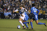 05 December 2008: North Carolina's Courtney Jones (in white) is held by UCLA's Dea Cook (behind) as Erin Hardy (12) follows the play. The University of North Carolina Tar Heels defeated the University of California Los Angeles Bruins 1-0 at WakeMed Soccer Park in Cary, NC in an NCAA Division I Women's College Cup semifinal game.