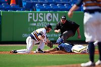 Canisius College Golden Griffins third baseman Liam Wilson (33) attempts to tag Cody Bruder (3) sliding head first into third base as umpire Robert Lothian looks on to make the call during the second game of a doubleheader against the Michigan Wolverines on February 20, 2016 at Tradition Field in St. Lucie, Florida.  Michigan defeated Canisius 3-0.  (Mike Janes/Four Seam Images)
