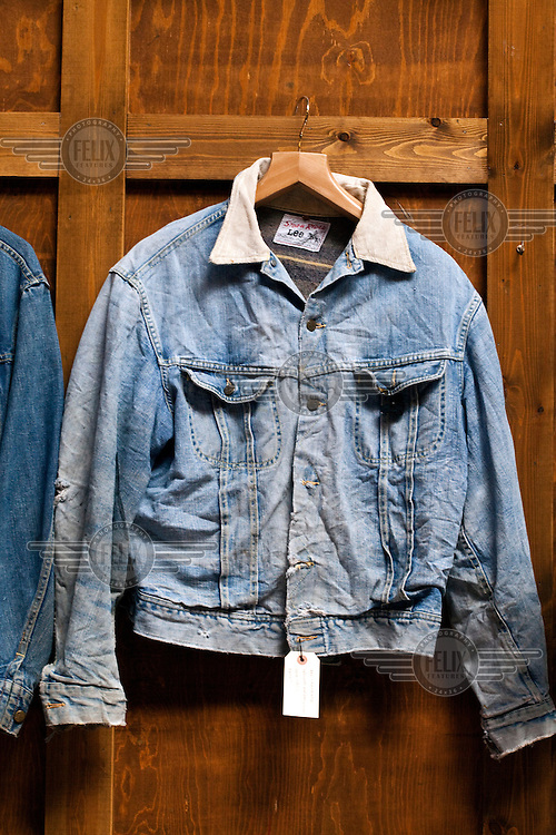 An old denim jacket hangs on a wall in the vintage clothes shop Blitz on Hanbury Street, Spitalfields, London.
