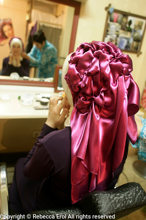 Woman having a special headscarf covering fitted at a hairdressers for a wedding celebration, Istanbul, Turkey
