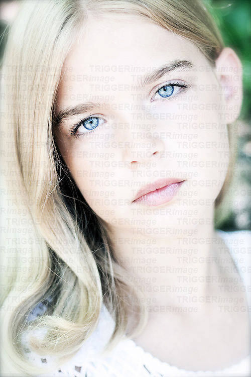 Young female youth with blonde hair and blue eyes looking into camera