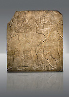 Assyrian relief sculpture panel  of Tribute bearers, the first one has a turban from north-west Syria and raises his clenched hands as a token of submission. The second person may be Phoenician and has a pair of monkeys to add the Assyrian kings exotic animal collection .  From Nimrud, Iraq,  865-860 B.C North West Palace. Court D, panel 7.  British Museum Assyrian  Archaeological exhibit no WA 124502.