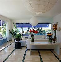 An area of the open-plan living room is furnished with white sofas while blue awnings protect the interior from the blinding afternoon sunlight through the picture windows