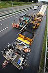 NIEUWEGEIN - Op de snelweg A2 tussen Nieuwegein en IJsselstein pelt een medewerker van Heijmans Wegenbouw uit Rosmalen rond koffietijd zijn eitje tijdens het asfalteren van de snelweg. Vanwege de aanleg van extra rijstroken en nieuwe afritten, wordt de zomerperiode gebruikt om de gehele snelweg van nieuw asfalt te voorzien, nadat eerder ondermeer nieuwe vangrails is gemonteerd. Terwijl 's avonds de helft van de rijbaan wordt afgesloten om het asfalt te verwijderen, wordt overdag het nieuwe wegdek aangelegd. Vanwege de veiligheid van de wegwerkers is de maximum snelheid beperkt, en zijn geleidebakens geplaatst. COPYRIGHT TON BORSBOOM
