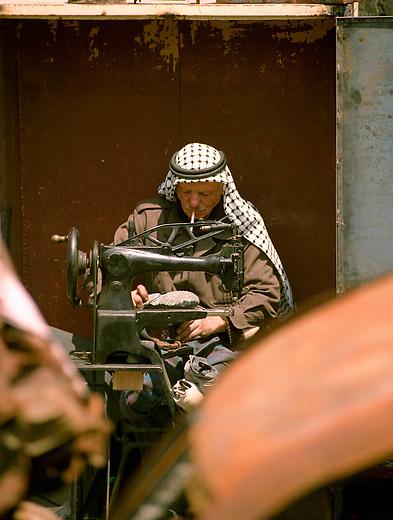 Strassenszene in Betlehem<br /> Immer wieder wird die palaestinensische Stadt Betlehem von der israelischen Armee belagert. Zum Teil tagelang duerfen die Bewohner ihre Haeuser nicht verlassen. Etliche Bewohner verloren bei den Kaempfen im April/Mai 2002 Angehoerige. Es gebe keine Familie in der heiligen Stadt, die nicht einen Toten zu beklagen habe, erzaehlen die Menschen. In den Tagen ohne israelische Soldaten, erweckt die Stadt einen normalen Anschein. Die Menschen gehen ihrem taeglichen Leben nach. Allerdings sind Touristen in diesen Tagen in der heiligen Stadt nicht zu sehen. Die Strassen sind so gut wie leer, die Wirtschaft liegt brach.<br /> Hier: Strassenszene in der Altstadt. Ein Schumacher arbeitet inmitten von zerbombten und ausgebrannten Autowracks.<br /> 19.05.2002, Betlehem<br /> Copyright: Christian-Ditsch.de<br /> [Inhaltsveraendernde Manipulation des Fotos nur nach ausdruecklicher Genehmigung des Fotografen. Vereinbarungen ueber Abtretung von Persoenlichkeitsrechten/Model Release der abgebildeten Person/Personen liegen nicht vor. NO MODEL RELEASE! Nur fuer Redaktionelle Zwecke. Don't publish without copyright Christian-Ditsch.de, Veroeffentlichung nur mit Fotografennennung, sowie gegen Honorar, MwSt. und Beleg. Konto: I N G - D i B a, IBAN DE58500105175400192269, BIC INGDDEFFXXX, Kontakt: post@christian-ditsch.de<br /> Bei der Bearbeitung der Dateiinformationen darf die Urheberkennzeichnung in den EXIF- und  IPTC-Daten nicht entfernt werden, diese sind in digitalen Medien nach &sect;95c UrhG rechtlich geschuetzt. Der Urhebervermerk wird gemaess &sect;13 UrhG verlangt.]