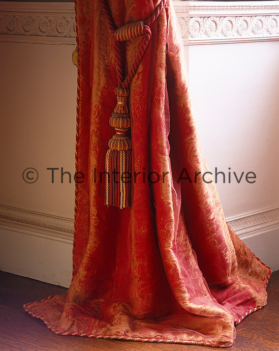 Detail of a red silk curtain and tassel tie-back in the library