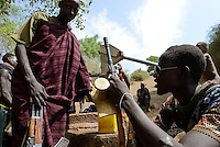 ETHIOPIA, Southern Nations, Lower Omo valley, Kangaten, village Kakuta, Nyangatom tribe, shepherds give water to their goats from water holes at dry river Kibish, a shepherd carry a Kalashnikov AK-47 machine gun, Made in China,  to protect themselves from cattle raids of Turkana tribe / AETHIOPIEN, Omo Tal, Kangaten, Dorf Kakuta, Nyangatom Hirtenvolk, Hirte mit Kalaschnikow AK-47 Maschinengewehr, Hergestellt in China,  zum Schutz vor Viehdiebstaehlen durch Turkana Voelker