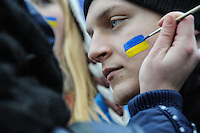 A protester is being  face painted with patriotic Ukrainian colors.<br /> Protesters did not give up after the faint  attempt of evacuation performed by the police of the night before. Despite the adverse weather conditions,  they restored and rebuilt the complex structures of the  barricades under the snow in Maidan square. Kiev,  Ukraine.