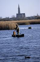 Europe/France/Pays de la Loire/44/Loire-Atlantique/Parc Naturel Régional de Brière/Ile Fedrun: Alain Divet installe les canards apelants - En fond le clocher de Saint-Joachim - Chasseur et chien de chasse sur une barque - AUTORISATION N°236