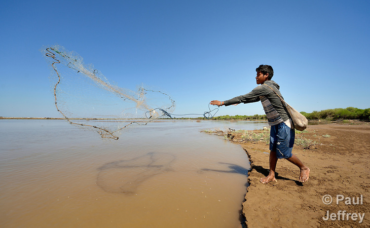 Jorge Pinto, a Wichi indigenous man, casts his fishing net into the Pilcomayo River in Santa Victoria Este, Argentina. The Wichi in this area, largely traditional hunters and gatherers, have struggled for decades to recover land that has been systematically stolen from them by cattleraisers and large agricultural plantations, and to preserve their access to a river which has suffered increasing levels of contamination from upstream mining and other uses. After years of negotiation supported by Church World Service, a landmark 2014 agreement will divide the land in this region between indigenous communities and settlers, guaranteeing the survival of the Wichi and their access to the river.