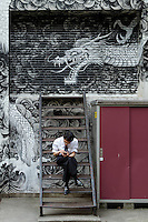 A Japanese salaryman or male office worker sits on steps to use a smart phone in Kabukicho, Shinjuku, Tokyo, Japan. Friday April 22nd 2016