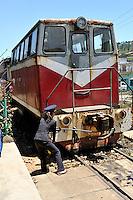 Female guard adjusting the coupling on a very old diesel locomotive. Da Lat Railway Station, Da Lat, Vietnam