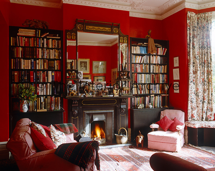 A roaring fire burns in a Victorian fireplace in this red-painted living room which is furnished with a matching pair of bookcases
