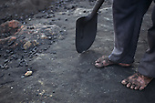 Rio Negro, Amazonas State, Brazil. The blackened feet of a charcoal worker, shovel.