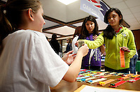 NWA Media/DAVID GOTTSCHALK - 12/18/14 - Talor Brinkmann, left to right, a seventh grade student at Oakdale Middle School in Rogers, collects the payment for charm bookmark from Lizbeth Pacheco and Ariana Garcia at the Global Marketplace presented by the REACH, reaching exceptional academic and creative heights, gifted and talented program Thursday December 18, 2014. Funds raised by the students will go towards payment of a field trip to the Heifer Learning Center at Heifer Ranch in Perryville.