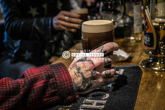 A customer's tattooed hand holds a pint of stout in a traditional Englsih pub in Essex.