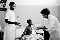 Mozambique. Province of Maputo. Manhiça is a small town (80 km north of the capital Maputo). A woman doctor from Brazil (expatriate) talks to a young girl seated in a bed while a nurse reads her medical file. The non governmental organisation (ngo) Médecins Sans Frontières (MSF) of Switzerland has rehabilitated the local hospital. © 1992 Didier Ruef