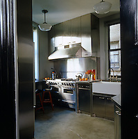 The industrial style kitchen has stainless steel appliances and units and a concrete floor