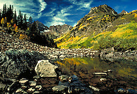 Fall landscape scene. The rocky shores of a lake and mountains, with bright, green vegitation and an evergreen grove growing on the surrounding hills. Scenic view, contrasts. Dramatic clouds in an azure blue sky. Colorado, Rocky Mountains.