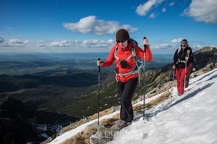 Two Female hikers cross snow near summit of Koscielec (2155m), Tatra mountains, Poland