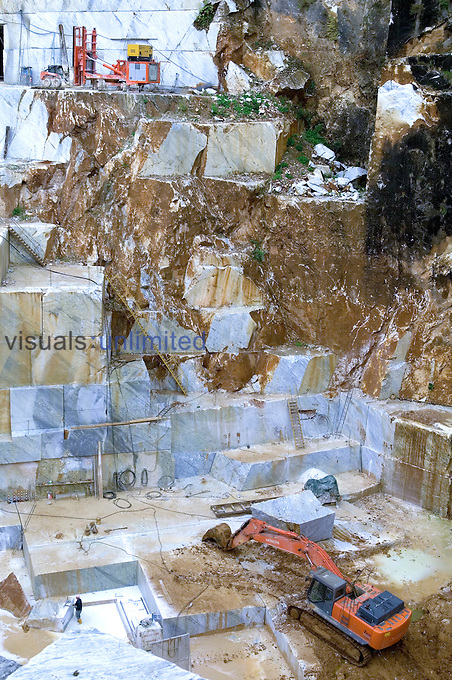 Miners and machines in marble quarry, Carrara, Alpi Apuane, Italy
