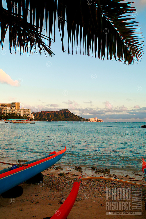 The front hulls of blue and red canoes line the sand during sunset at Waikiki Beach with Diamond Head in the distance.