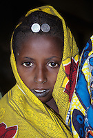 Tonkassare, Niger. A Fulani Girl, with two five-pesewa (Nigerian) coins in her hair as jewelry.  The girl is from Niger.  The coins are from Nigeria, the country to the south.