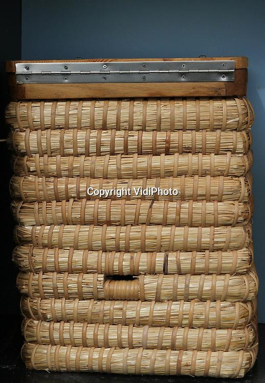 Foto: VidiPhoto..SPEULD - Leden van de Uddelse bijenvereniging De Vierkante Korf, tonen in Speuld op de Veluwe de enige rijdende bijenstal van Nederland. Tussen de soms 200 jaar oude bijenkorven, staan nieuw vervaardigde replica's. Totaal zo'n 40 stuks.De imkerverenging gebruikt de rijdende 'stal' voor educatie op bijenmarkten en (jaar)markten, om zo anderen te interesseren voor het het vak van imker, dat met 'uitsterven' wordt bedreigd. Ook worden er cursussen korfvlechten gegeven in de wintermaanden.