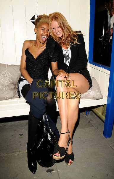 TOLULA ADEYEMI & OLIVIA INGE.The Neal's Yard Remedies Natural Beauty Honours, Neal's Yard Remedies store, King's Road, London, England..September 4th, 2008.full length black sitting off the shoulder hand wedges legs crossed cellulite mouth open.CAP/CAN.©Can Nguyen/Capital Pictures.