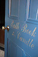 The words bath, book and candle decorate a blue door with a brass handle, which leads to a bathroom