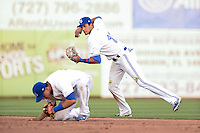 Dunedin Blue Jays  shortstop Emilio Guerrero (13) throws to first as second baseman Christian Lopes (14) ducks out of the way during a game against the Brevard County Manatees on April 11, 2014 at Florida Auto Exchange Stadium in Dunedin, Florida.  Brevard County defeated Dunedin 5-2.  (Mike Janes/Four Seam Images)