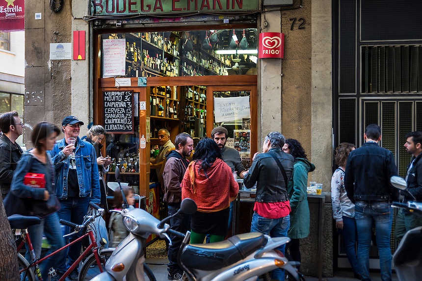 Bodega patrons spill out into the street to socialize and consume wine and beer, Barcelona, Spain