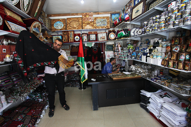 A Palestinian man displays a traditional goods marking the Palestinian traditional customs day, in Gaza City, on July 30, 2019. Photo by Mahmoud Ajjour