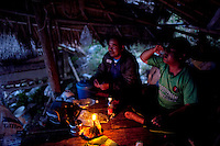 "Nil, 52, left, and Uten, 30, drink Laos whiskey by candle light in their fishing hut on the Mekong River in Sop Ruak, Thailand. Nil says that prices in town keep getting hirer as development increase.  But the fish are few in numbers and the water low in inconsistent due to the dams in China he said. ""I wish it was like 7-8 years ago when there were a lot more fish,"" he said. Photo taken on Thursday, December 10, 2009. Kevin German / Luceo Images"