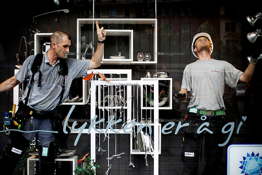"Oslo, Norway, 23.07.2011. Workers are mounting new windows in a shopping mall close to where the bomb went off. The writing on the window reads ""happiness is giving"". The morning in Oslo was dedicated to cleaning up shattered glass all over the city. Oslo awakes to shocking messages of the total bodycount after yesterdays massacre. A total of 91 persons were killed in the massacre in Utøya right outside Oslo. Seven of those died when a car bomb was detonated outside the main government biuilding in the heart of Oslo, friday 22. of July. Foto: Christopher Olssøn."