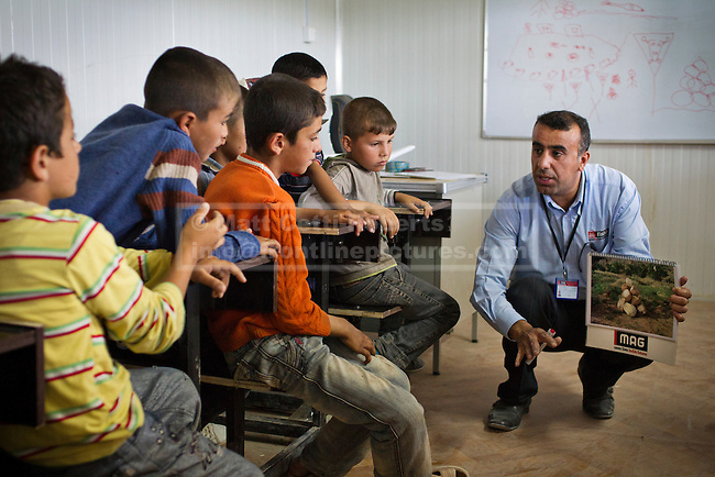 A member of a Mines Advisory Group (MAG) community liaison team gives a mine risk education session at School Number 3 to Syrian refugee children in the Domiz Refugee a camp near Dohuk, Iraqi-Kurdistan. Many of the children passed through areas containing mines and unexploded ordnance when escaping the ongoing civil war in Syria and may return to the country periodically with their families. The camp, run by the UNHCR and International Rescue Committee, is situated on the site of an old Iraqi Army base that was bombed during the 2003 coalition forces invasion of Iraq and was cleared by MAG before being set up, unexploded ordnance is still found in the surrounding hills.