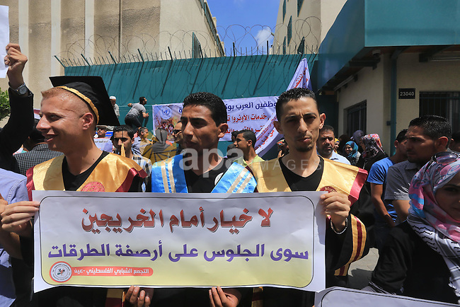 Palestinians hold banners during a protest against the UNRWA decision to reduce of the aid in front of the headquarters United Nations Relief and Works Agency (UNRWA), in Gaza city on June 14, 2015. Photo by Mohammed Asad
