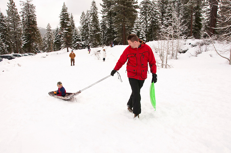 California, Lake Tahoe: Child and father enjoy snow play with sled at North Lake Tahoe Regional Park.  Photo copyright Lee Foster.  Photo # cataho107500
