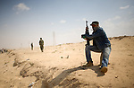 Rebels patrolled the desert near the city of Ajdabiya, Libya, March 24, 2011. Despite air strikes from Western war planes, which crippled Col. Muammar Qaddafi's military capability, the rebels seemed unable to advance and retake the city.