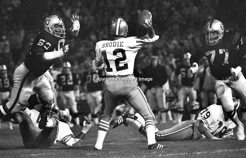 SF 49ers John Brodie is rushed by Oakland Raiders Otis Sistrunk and #77 Bubba Smith. (1973 photo/Ron Riesterer)