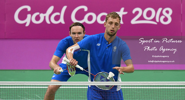 Patrick MACHUGH (SOC) serves, watched by Martin CAMPBELL (SOC) in the mens doubles. Badminton. Mixed team event. XXI Commonwealth games. Carrara Sports hall 2. Gold Coast 2018. Queensland. Australia. 05/04/2018. ~ MANDATORY CREDIT Garry Bowden/SIPPA - NO UNAUTHORISED USE - +44 7837 394578