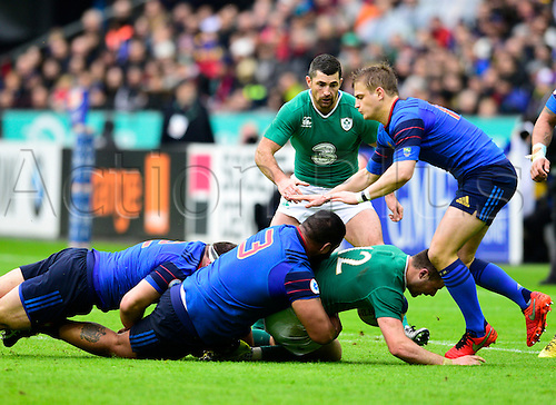 13.02.2016. Stade de France, Paris, France. 6 Nations Rugby international. France versus Ireland.  Robbie Henshaw ( Ireland ) brought down by Uini Atonio ( France ) and Jules Plisson ( France )