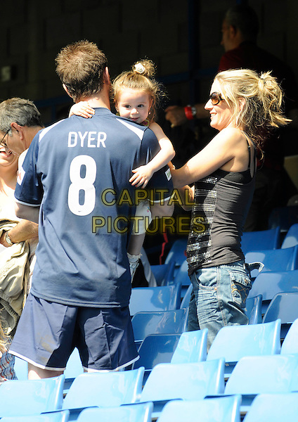SUNNIE, DANNY DYER & JOANNE MAS .Celebrity Soccer Six in aid of The Samaritans held at Chelsea Football ground, Stamford Bridge, London, England..May 24th 2009 .football match game half length blue top carrying lifting dad father family kid child side view profile back behind rear  couple mother mom mum .CAP/FIN.©Steve Finn/Capital Pictures.